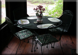 Table and chairs on screened porch.